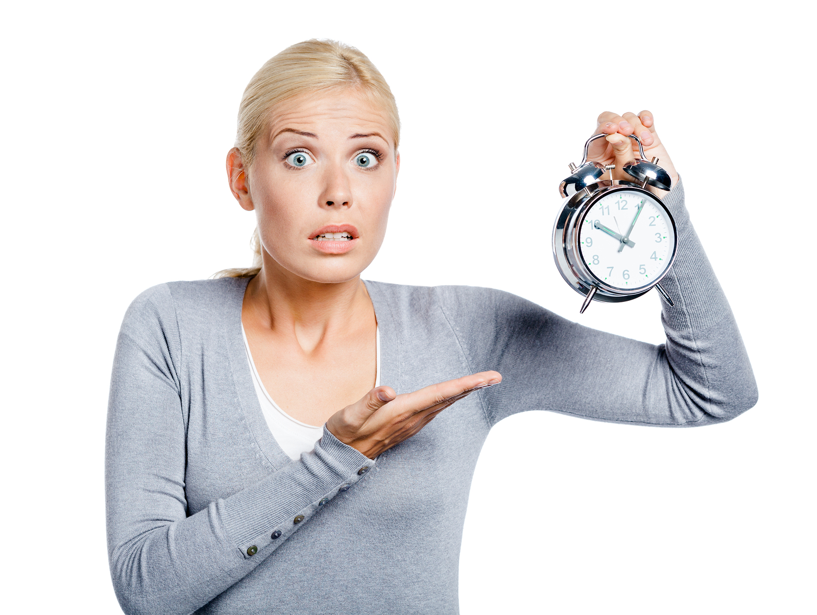 Worried woman in grey pullover pointing at the alarm clock, isol