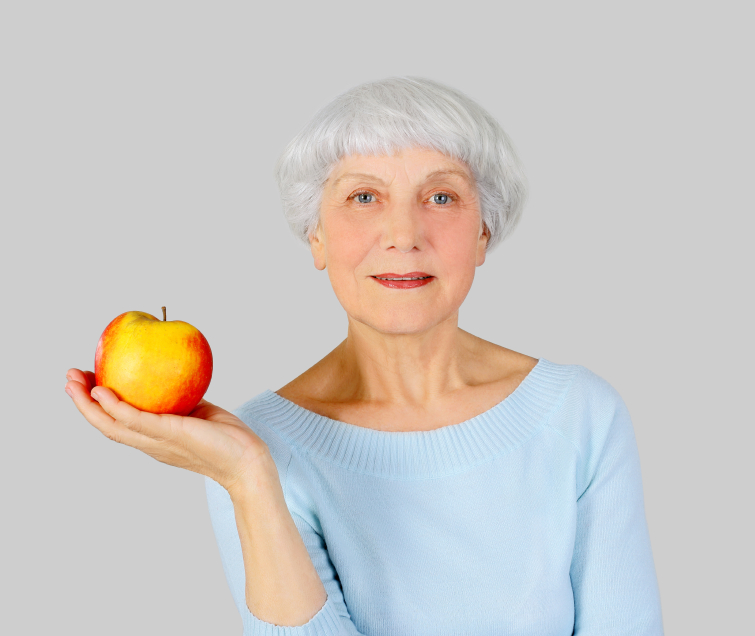 elderly woman with red apple in hands on a light background in t