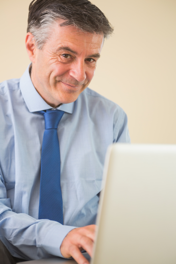 Pleased mature man using a laptop sitting on a bed in a bedroom