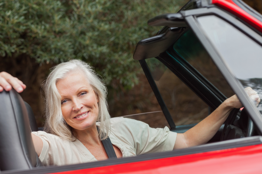 Smiling mature woman posing in red convertible on sunny day