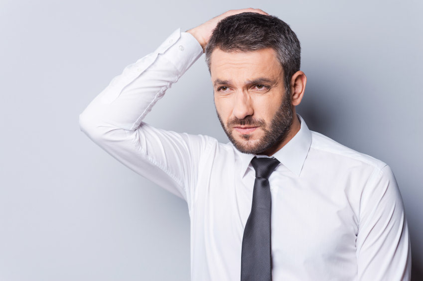 Feeling uncertain. Frustrated mature man in shirt and tie holding hand in hair and looking away while standing against grey background
