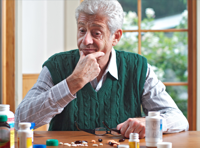 Thoughtful senior man looks at his many pills